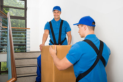 Two Male Movers In Uniform Standing With Box On Staircase